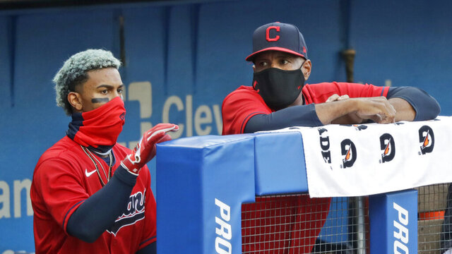 Cleveland Indians acting manager Sandy Alomar Jr., right, talks with Francisco Lindor during the first inning in a baseball game against the Cincinnati Reds, Wednesday, Aug. 5, 2020, in Cleveland. (AP Photo/Tony Dejak)