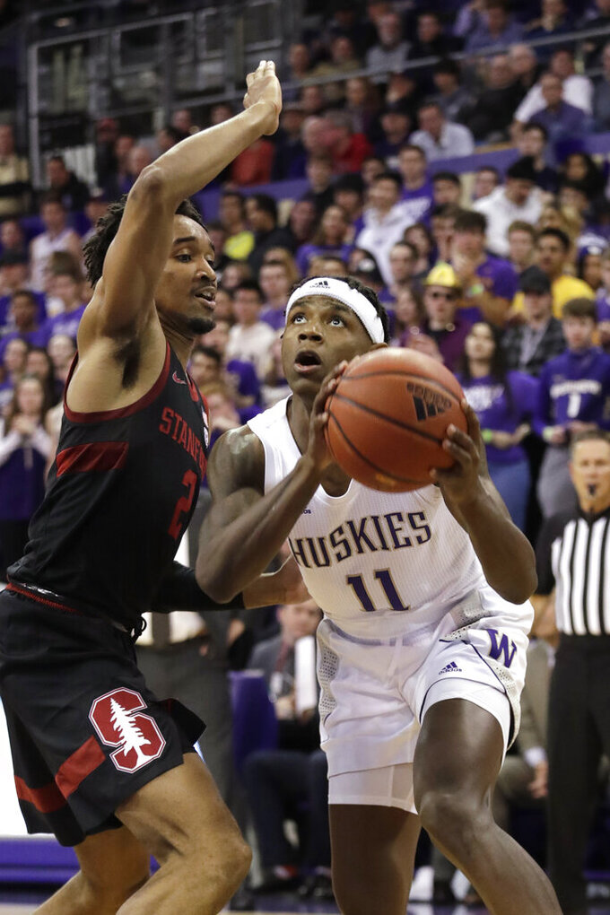 Washington's Nahziah Carter (11) tries to get past Stanford's Bryce Wills during the first half of an NCAA college basketball game Thursday, Feb. 20, 2020, in Seattle. (AP Photo/Elaine Thompson)