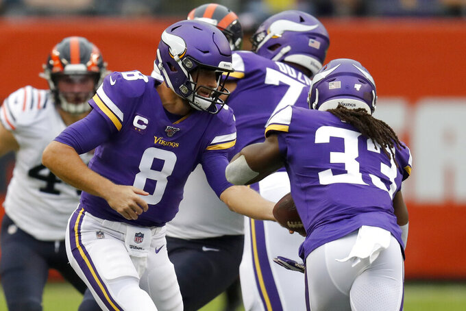 Minnesota Vikings quarterback Kirk Cousins (8) hands off to running back Dalvin Cook (33) during the half of an NFL football game against the Chicago Bears Sunday, Sept. 29, 2019, in Chicago. (AP Photo/Charles Rex Arbogast)
