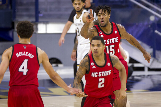 North Carolina State's Manny Bates (15) celebrates after a basket as teammates Jericole Hellems (4) and Shakeel Moore (2) head downcourt during the second half of an NCAA college basketball game against Notre Dame on Wednesday, March 3, 2021, in South Bend, Ind. North Carolina State won 80-69. (AP Photo/Robert Franklin)