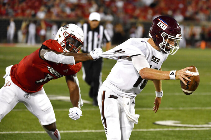 Louisville linebacker Monty Montgomery (7) grabs the jersey of Eastern Kentucky quarterback Parker McKinney (18) during the first half of an NCAA college football game in Louisville, Ky., Saturday, Sept. 11, 2021. (AP Photo/Timothy D. Easley)