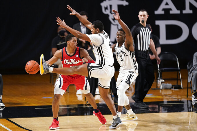 Mississippi's Matthew Murrell, left, is defended by Vanderbilt's Jordan Wright (4) and Maxwell Evans (3) in the first half of an NCAA college basketball game Saturday, Feb. 27, 2021, in Nashville, Tenn. (AP Photo/Mark Humphrey)