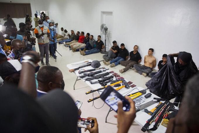 FILE - In this July 8, 2021 file photo, suspects in the assassination of Haiti's President Jovenel Moise are shown to the media, along with the weapons and equipment they allegedly used in the attack, at police headquarters in Port-au-Prince, Haiti.  Former Colombian soldiers arrested in Haiti in the assassination have accused local authorities of torture, saying they've been burned, stabbed and hit in the head with a hammer, among other things, in a Wednesday, Sept. 6 letter, addressed to Colombia's president and other high-ranking officials as well as the Inter-American Court of Human Rights and the International Committee of the Red Cross. It was signed by the 18 former soldiers arrested in the slaying. (AP Photo/Joseph Odelyn, File)