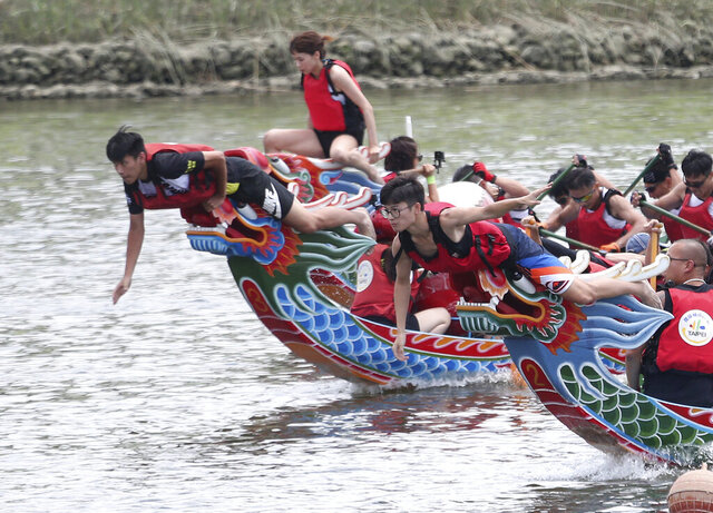 Crew leaders prepare to grab finish line flags during the traditional Chinese dragon boat race in Taipei, Taiwan, Thursday, June 25, 2020. Dragon boat races are in remembrance of Chu Yuan, an ancient Chinese scholar-statesman, who drowned in 277 B.C. while denouncing government corruption. (AP Photo/Chiang Ying-ying)