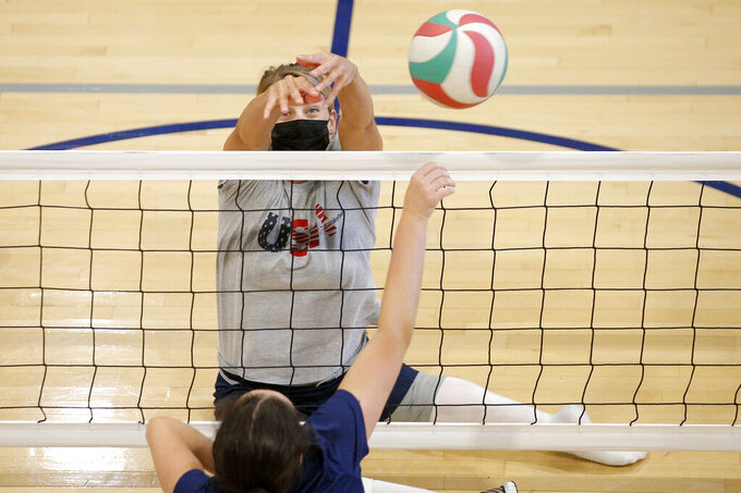 Lora Webster with the U.S. women's sitting volleyball team, tries to block the ball during a practice in Edmond, Okla., on July 24, 2021. She's five months pregnant and expecting her fourth child. This is the second Paralympics in which she's been pregnant, and the third time during a competition. She and her American teammates face Brazil on Friday, Sept. 3, 2021, in the semifinals as Webster tries for her fifth Paralympic medal. (Bryan Terry/The Oklahoman via AP)