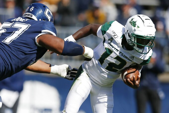 South Florida quarterback Jordan McCloud (12) breaks away from Connecticut defensive lineman Travis Jones (57) during the first half of an NCAA college football game in East Hartford, Conn., Saturday, Oct. 5, 2019. (AP Photo/Michael Dwyer)