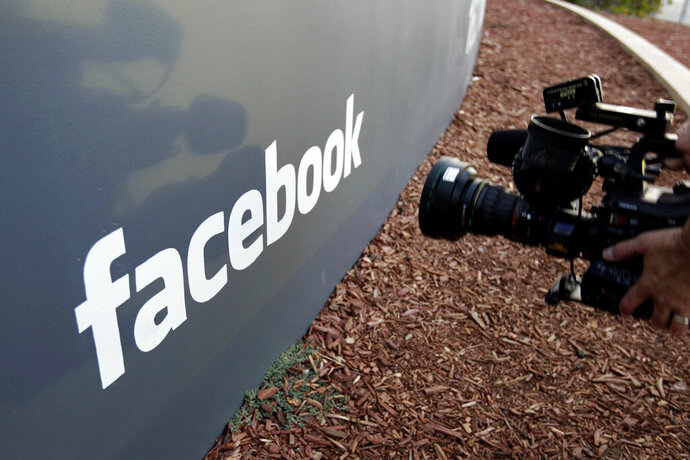 FILE - In this May 18, 2012, file photo a television photographer shoots the sign outside of Facebook headquarters in Menlo Park, Calif. A parliamentary committee report published Sunday, Feb. 17, 2019, has recommended that the United Kingdom government increase oversight of social media platforms like Facebook to better control harmful or illegal content. (AP Photo/Paul Sakuma, File)