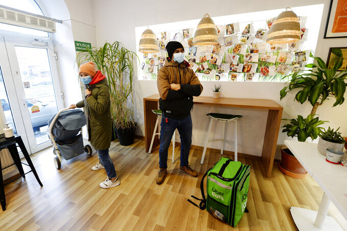 Venezuela's 2012 Olympic champion in fencing, Ruben Limardo Gascon, waits at a sushi bar for food he is to home-deliver as part of his job for Uber Eats, in Lodz, Poland, Saturday, Nov. 14, 2020. Limardo Gascon needs the food delivery job to support his family as lives and trains in Poland and plans to win a medal at Tokyo Olympics.(AP Photo/Czarek Sokolowski)