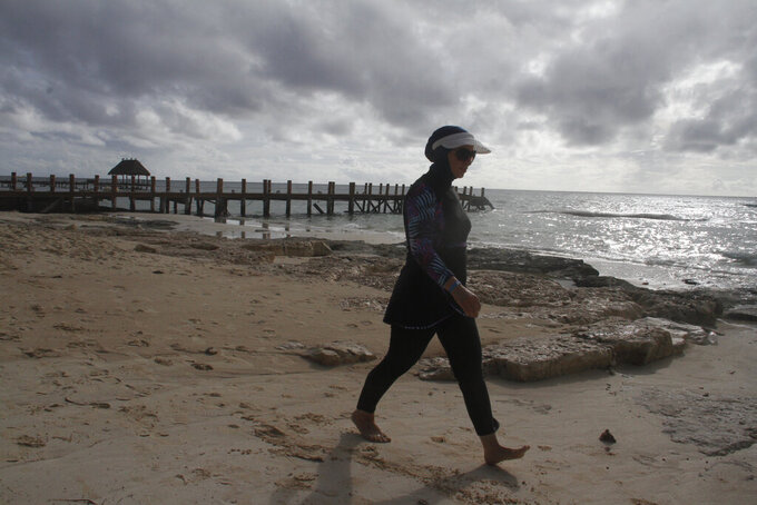 Zena Koudsi, from Charlotte, North Carolina, walks on the beach near Playa del Carmen, Mexico before Hurricane Delta arrives, early Tuesday, Oct. 6, 2020. Hurricane Delta rapidly intensified into a Category 2 hurricane Tuesday on a course to hammer southeastern Mexico and then grow to a potentially catastrophic Category 4 on approach to the U.S. Gulf Coast this week. (AP Photo/Tomas Stargardter)
