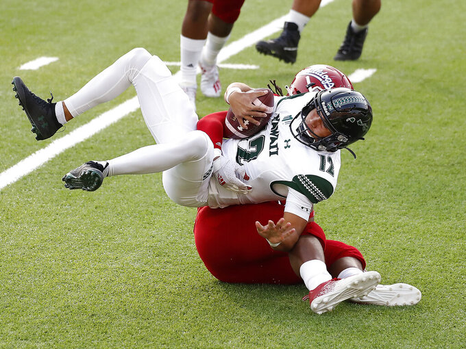 Hawaii quarterback Chevan Cordeiro, top, is sacked by Fresno State defensive end Kwami Jones during the first half of an NCAA college football game in Fresno, Calif., Saturday, Oct. 24, 2020. (AP Photo/Gary Kazanjian)
