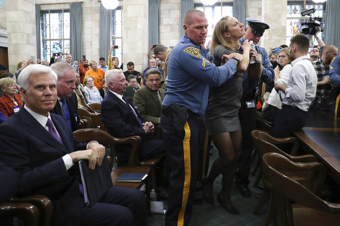 New Jersey State Police remove Sue Altman, state director, New Jersey Working Families, before George E. Norcross III, left, testifies in front of the New Jersey Senate Select Committee on Economic Growth Strategies about his role in the controversial state tax incentive program, Monday, Nov. 18, 2019, in Trenton, N.J. (David Maialetti/The Philadelphia Inquirer via AP)