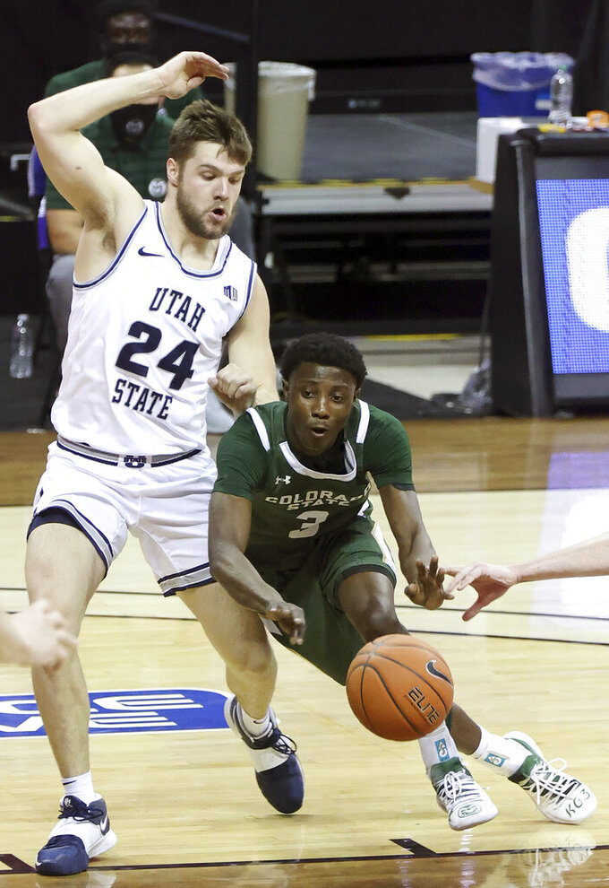 Colorado State guard Kendle Moore (3) passes as Utah State guard Rollie Worster (24) defends during the second half of an NCAA college basketball game in the semifinal round of the Mountain West Conference men's tournament Friday, March 12, 2021, in Las Vegas. (AP Photo/Isaac Brekken)
