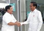 Indonesian President Joko Widodo, right, shares a light moment with his defeated election rival Prabowo Subianto during their meeting at a subway station in Jakarta, Indonesia, Saturday, July 13, 2019. Widodo and the former special forces general met for the first time since the divisive April poll, signaling a calming of political tensions in the world's third-largest democracy. (AP Photo/Dita Alangkara)