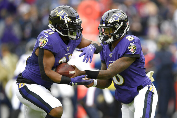 Baltimore Ravens quarterback Lamar Jackson (8) hands off to running back Mark Ingram (21) during the first half of an NFL football game against the Houston Texans, Sunday, Nov. 17, 2019, in Baltimore. (AP Photo/Nick Wass)