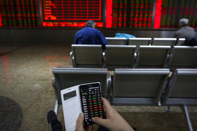 A man checks stock prices through his smartphone at a brokerage house in Beijing, Tuesday, Jan. 22, 2019. Asian markets were mostly lower on Tuesday after the International Monetary Fund trimmed its global outlook for 2019 and 2020. This came after China said its economy grew at the slowest pace in 30 years. (AP Photo/Andy Wong)