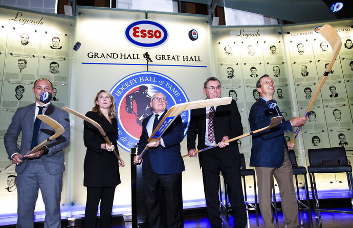 FILE - In this Nov. 15, 2019, file photo, Hockey Hall of Fame inductees, from left, Sergei Zubov, Hayley Wickenheiser, Jim Rutherford, Vaclav Nedomansky and Guy Carbonneau flip pucks in the air during a ceremony in Toronto. The Hockey Hall of Fame has postponed its 2020 induction because of the pandemic. The ceremony was to have taken place Nov. 16 in Toronto. (Nathan Denette/The Canadian Press via AP, File)