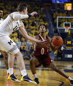Michigan center Jon Teske (15) reaches in on Elon guard Hunter McIntosh (0) during the first half of an NCAA college basketball game Friday, Nov. 15, 2019, in Ann Arbor, Mich. (AP Photo/Carlos Osorio)
