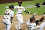 San Diego Padres' Jurickson Profar, second from left, celebrates after scoring off a three-RBI double by Eric Hosmer during the seventh inning of a baseball game against the Arizona Diamondbacks, Friday, July 24, 2020, in San Diego. (AP Photo/Gregory Bull)