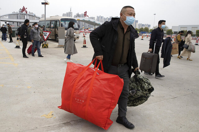 Residents carry their belongings as they walk past a toll booth to enter the city of Wuhan which is still under lockdown due to the coronavirus outbreak but have started allowing some residents to return in central China's Hubei province on Thursday, April 2, 2020. (AP Photo/Ng Han Guan)