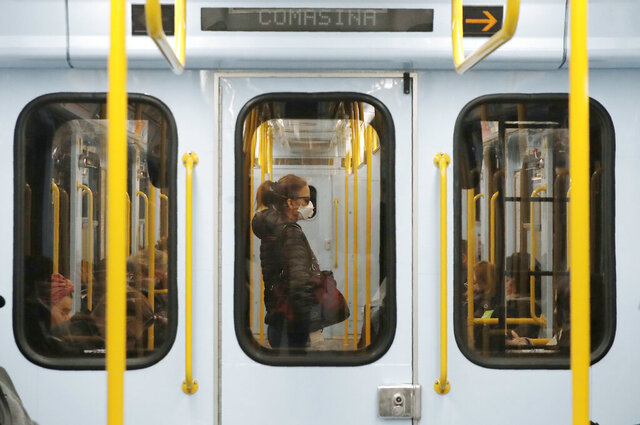 FILE - In this Thursday, March 5, 2020 file photo, a woman wearing a face mask stands in a subway train in Milan, Italy. The focal point of the coronavirus emergency in Europe, Italy, is also the region's weakest economy and is taking an almighty hit as foreigners stop visiting its cultural treasures or buying its prized artisanal products, from fashion to food to design. Europe's third-largest economy has long been among the slowest growing in the region and is the one that is tallying the largest number of virus infections outside Asia. (AP Photo/Antonio Calanni, File)