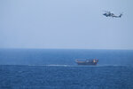 A U.S. Navy Seahawk helicopter flies over a stateless dhow later found to be carrying a hidden arms shipment in the Arabian Sea on Thursday, May 6, 2021. The U.S. Navy announced Sunday it seized the arms shipment hidden aboard the vessel in the Arabian Sea, the latest-such interdiction by sailors amid the long-running war in Yemen. (U.S. Navy via AP)