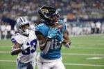 Jacksonville Jaguars wide receiver Laviska Shenault Jr. (10) catches a pass for a touchdown as Dallas Cowboys cornerback Deante Burton (33) defends in the first half of a preseason NFL football game in Arlington, Texas, Sunday, Aug. 29, 2021. (AP Photo/Ron Jenkins)