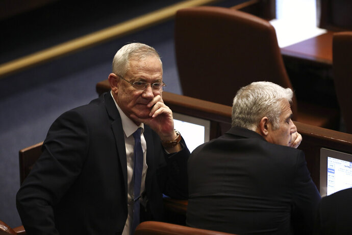 Blue and White party leaders Benny Gantz, left, and Yair Lapid attend a Knesset session in Jerusalem, Wednesday, Dec. 11, 2019. The Israeli parliament began voting to dissolve itself on Wednesday and pave the path to an unprecedented third election within a year. (AP Photo/Oded Balilty)