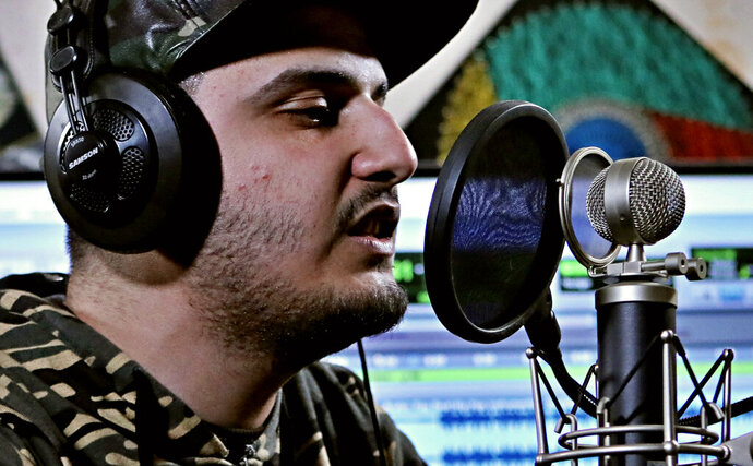 In this Tuesday, Feb. 12, 2019 photo, rapper Ahmed Chayeb, better known by his stage name Mr. Guti, records on his computer, at his home in the southern port city of Bqasra, Iraq. Chayeb raps about anger and disillusionment in his hometown of Basra, which saw riots last summer over failing services and soaring unemployment. Chayeb says his generation is fed up with the false piety of politicians and religious authorities who preach about faith and duty but have left Basra to fall apart. (AP Photo/Nabil al-Jurani)