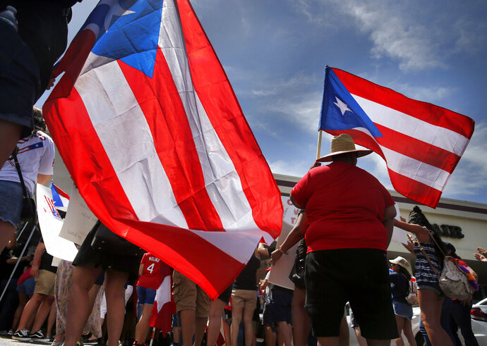 About 200-300 people from the North Texas (Dallas-Fort Worth area) Puerto Rican community gather to protest Gov. Ricardo Rossello outside the Adobo Puerto Rican Cafe in Irving, Texas, Sunday, July 21, 2019. Puerto Rico's embattled governor says he will not seek re-election but will not resign as the island's leader, though he will step down as head of his pro-statehood party. (Tom Fox/The Dallas Morning News via AP)