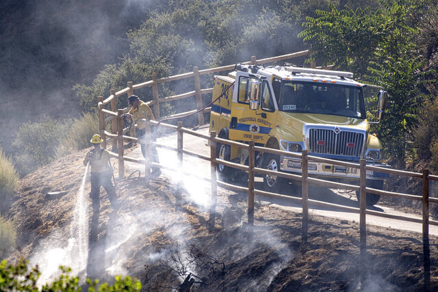 FILE - In this Monday, July 6, 2020 file photo, firefighters douse hot spots along Agua Dulce Canyon road in Agua Dulce, Calif. Emergency personnel are working through high temperatures to contain the Soledad fire in Southern California. In early July 2020, meteorologists say temperatures will be stuck with above normal temperatures through the month if not longer. (David Crane/The Orange County Register via AP)