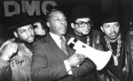 "FILE - In this Feb. 11, 1988, file photo, Joe Clark, principal of Eastside High School in Paterson, N.J., stands with rap group Run-DMC before the group gave a concert at the school in support of Clark's way of running his school. Clark, the baseball bat and bullhorn-wielding principal whose unwavering commitment to his students and uncompromising disciplinary methods inspired the 1989 film ""Lean on Me,"" died at his Florida home on Tuesday, Dec. 29, 2020, after a long battle with an unspecified illness, his family said in statement. He was 82. (AP Photo/Peter Cannata, File)"