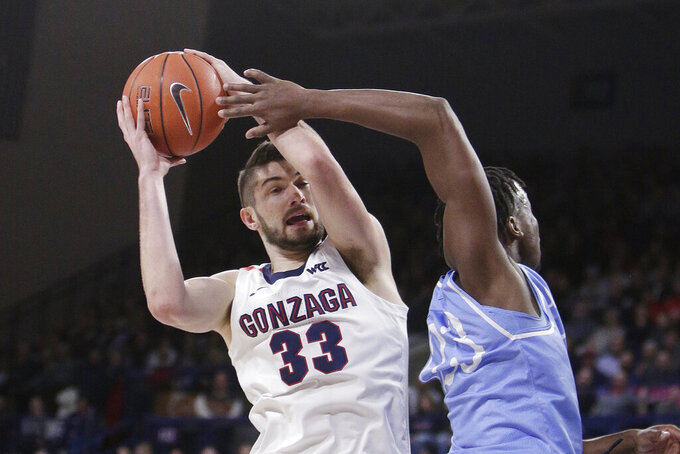 Gonzaga forward Killian Tillie (33) grabs a rebound next to San Diego forward James Jean-Marie (23) during the first half of an NCAA college basketball game in Spokane, Wash., Thursday, Feb. 27, 2020. (AP Photo/Young Kwak)