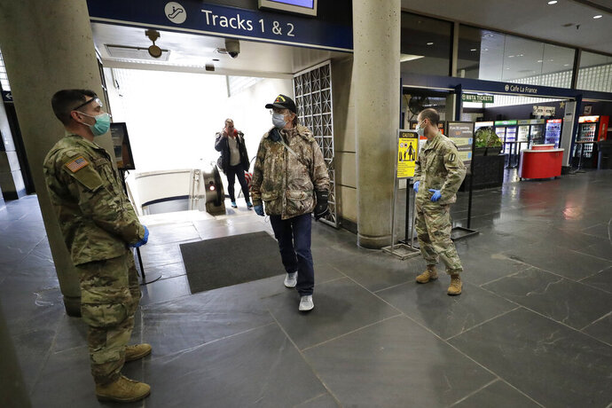 Members of the Rhode Island National Guard, left, and right, greet disembarking train passengers, Monday, March 30, 2020, at Providence Station train station, in Providence, R.I., to provide them with information about the coronavirus and advise them to self-quarantine for 14 days if they are arriving from out of state. The new coronavirus causes mild or moderate symptoms for most people, but for some, especially older adults and people with existing health problems, it can cause more severe illness or death. (AP Photo/Steven Senne)