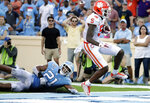 Clemson's Tee Higgins (5) dodges the tackle of North Carolina's Chazz Surratt (21) to score the team's final touchdown during the fourth quarter of an NCAA college football game in Chapel Hill, N.C., Saturday, Sept. 28, 2019. (AP Photo/Chris Seward)