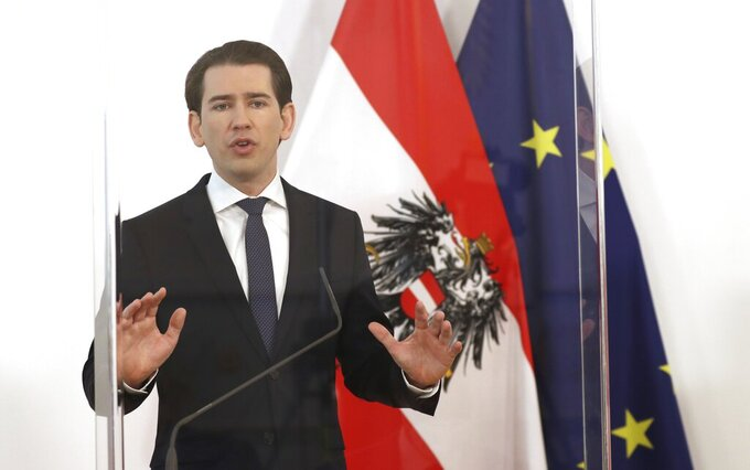 Austrian Chancellor Sebastian Kurz speakes behind plexiglass shields at a press conference at the federal chancellery in Vienna, Austria, Wednesday, Dec. 2, 2020. The Austrian government has moved to restrict freedom of movement for people, in an effort to slow the onset of the COVID-19 coronavirus. (AP Photo/Ronald Zak)