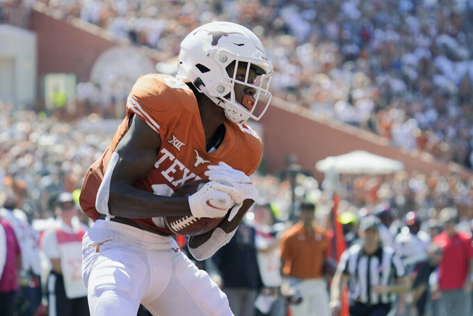 Texas wide receiver Xavier Worthy (8) catches a touchdown pass against Texas Tech during the first half of an NCAA college football game on Saturday, Sept. 25, 2021, in Austin, Texas. (AP Photo/Chuck Burton)