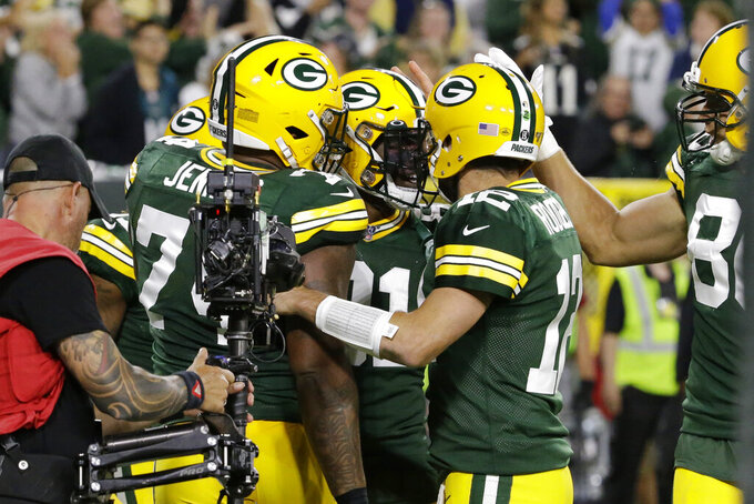 Green Bay Packers wide receiver Geronimo Allison (81) celebrates a catch for a touchdown with quarterback Aaron Rodgers (12) and offensive guard Elgton Jenkins (74) during the first half of an NFL football game against the Philadelphia Eagles on Thursday, Sept. 26, 2019, in Green Bay, Wis. (AP Photo/Mike Roemer)
