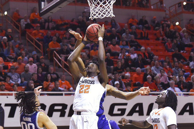 Kansas State guard Mike McGuirl (0) and Oklahoma State forward Cameron McGriff (12) watch as Oklahoma State forward Kalib Boone (22) shoots during the first half of an NCAA college basketball game in Stillwater, Okla., Wednesday, March 4, 2020. (AP Photo/Brody Schmidt)