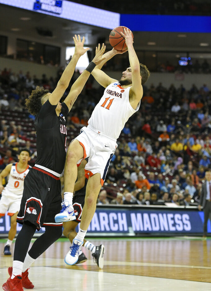 Virginia's Ty Jerome (11) shoots over Gardner-Webb's Jose Perez (5) during a first-round game in the NCAA men's college basketball tournament in Columbia, S.C., Friday, March 22, 2019. (AP Photo/Richard Shiro)