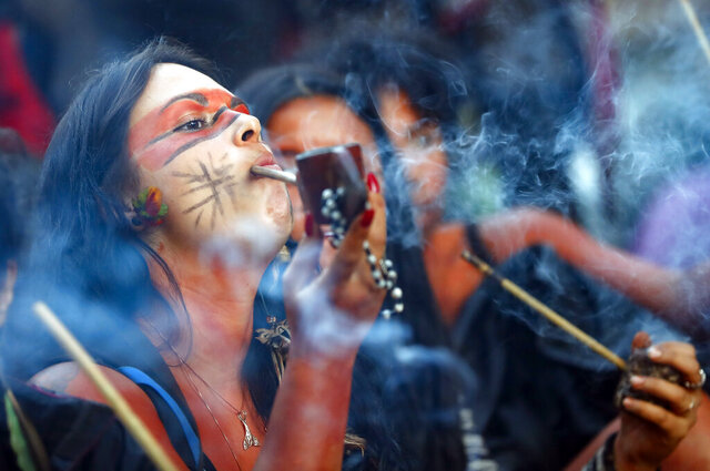 A member of the Guarani Mbya indigenous tribe smokes a pipe while waiting for police to enter the property the group has been occupying for just over a month in an attempt to stop real estate developer Tenda from constructing apartment buildings next to their community's land in Sao Paulo, Brazil, early Tuesday, March 10, 2020. Sao Paulo police are set to force the expulsion of members of this tiny indigenous tribe on Tuesday. (AP Photo/Andre Penner)