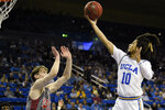 UCLA guard Tyger Campbell (10) goes up to shoot in front of Utah forward Mikael Jantunen during the first half of an NCAA college basketball game in Los Angeles, Sunday, Feb. 2, 2020. (AP Photo/Kelvin Kuo)