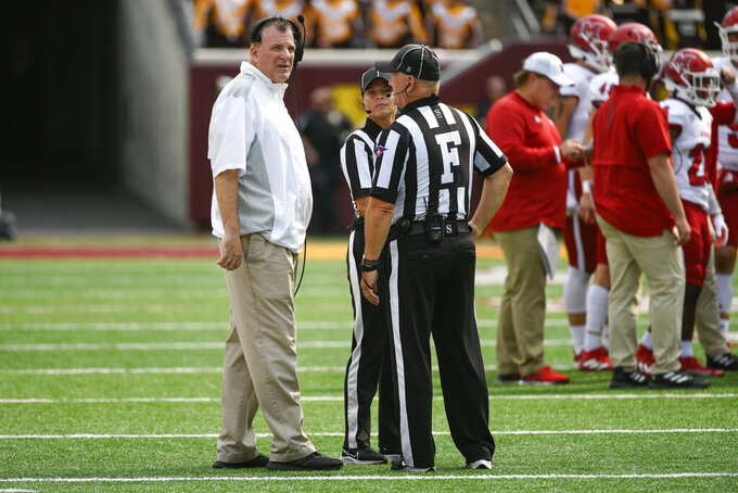 Miami-Ohio head coach Chuck Martin, left, talks with the game officials during a break in the first half of an NCAA college football game against Minnesota Saturday, Sept. 11, 2021, in Minneapolis. Minnesota won 31-26. (AP Photo/Craig Lassig)