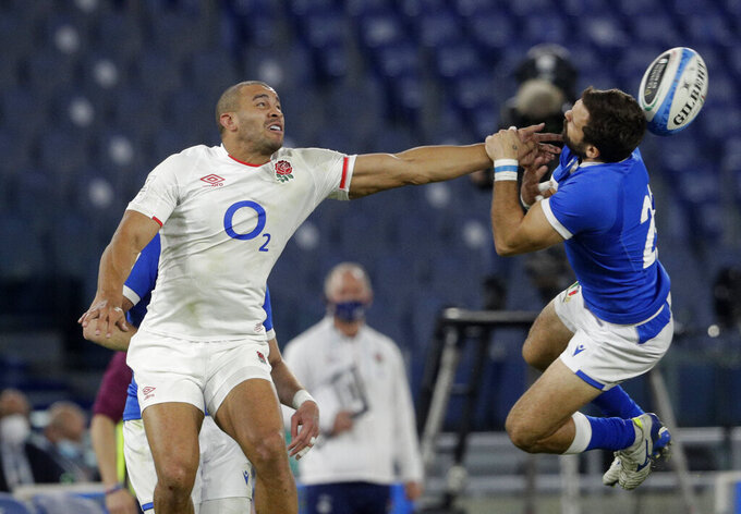 England's Jonathan Joseph, left, and Italy's Guglielmo Palazzani leap for a loose ball during the Six Nations rugby union international match between Italy and England at the Olympic Stadium in Rome, Italy, Saturday, Oct. 31, 2020. (AP Photo/Gregorio Borgia)