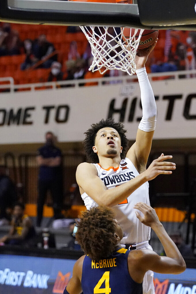 Oklahoma State guard Cade Cunningham, top, shoots over West Virginia guard Miles McBride (4) in the second half of an NCAA college basketball game Monday, Jan. 4, 2021, in Stillwater, Okla. (AP Photo/Sue Ogrocki)