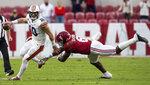 Auburn quarterback Bo Nix (10) gets away from the tackle of Alabama linebacker Christian Harris (8) during an NCAA college football game Saturday, Nov. 28, 2020, in Tuscaloosa, Ala. (Mickey Welsh/The Montgomery Advertiser via AP)
