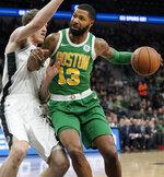 Boston Celtics' Marcus Morris (13) drives against San Antonio Spurs' Jakob Poeltl during the first half of an NBA basketball game, Monday, Dec. 31, 2018, in San Antonio. (AP Photo/Darren Abate)