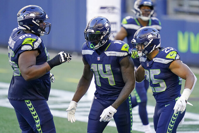 Seattle Seahawks wide receiver DK Metcalf (14) celebrates with Jordan Simmons, left, and Travis Homer, right, after Metcalf scored a touchdown during the second half of an NFL football game, Sunday, Sept. 27, 2020, in Seattle. The Seahawks won 38-31. (AP Photo/Elaine Thompson)