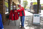 Tom Latournous tries on a jacket outside Art's for Him and Her Too clothing store in downtown Honesdale, Pa. on Friday, May 22, 2020. Many Wayne County businesses opened on Friday for the first time since March as the county moved to the yellow phase of reopening after the COVID-19 shutdown of non-essential businesses. (Christopher Dolan/The Times-Tribune via AP)
