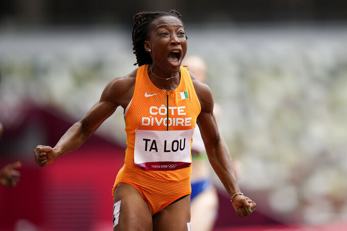 Marie-Josee Ta Lou, of the Ivory Coast, wins a heat in the women's 100-meter run at the 2020 Summer Olympics, Friday, July 30, 2021, in Tokyo. (AP Photo/Petr David Josek)