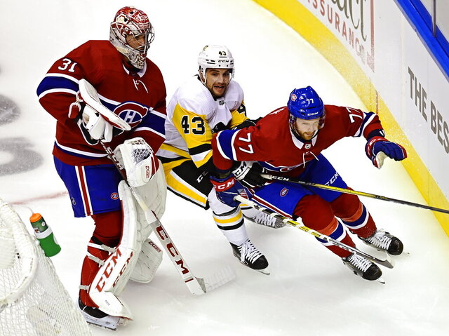 Montreal Canadiens goaltender Carey Price (31) stays out of the way as Pittsburgh Penguins' Conor Sheary (43) chases Canadiens' Brett Kulak (77) during first period NHL Eastern Conference Stanley Cup playoff action in Toronto on Wednesday, Aug. 5, 2020. (Frank Gunn/The Canadian Press via AP)